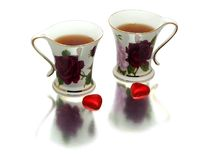 Two tea cups. With two heart shaped candies royalty free stock photos