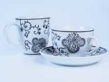 Two tea cups decorated with designs isolated on white background Royalty Free Stock Photos