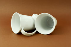 Two tea cups laying on brown background.  Royalty Free Stock Image