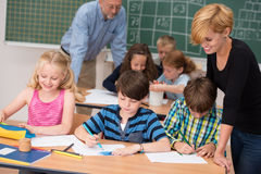 Two teachers in class with their young students. With a beautiful young women helping two small boys and a girl at a desk in the front with a male teacher Royalty Free Stock Photography