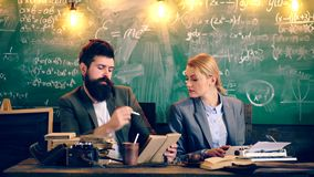 Two teachers are intelligently dressed engaged in a school classroom on the background of a green board. Teacher in stock video