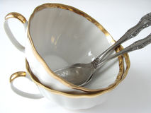 Two teacups. Two white teacups with golden border and two teaspoons Royalty Free Stock Photography