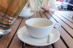 Two teacups and French press on the table, blurred woman behind. Pouring tea concept. royalty free stock photography