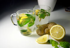 Two teacups with fresh peppermint, ginger and lemon Royalty Free Stock Photos