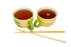 Two teacups with tea and chopsticks Stock Image
