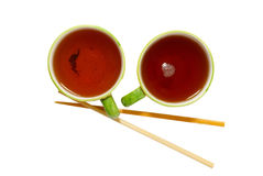 Two teacups with tea and chopsticks Royalty Free Stock Image