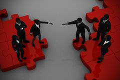 Two teams Merging on a red jigsaw puzzle. Two teams of executives merging on a jigsaw puzzle showing a partnership and collaboration Royalty Free Stock Photography