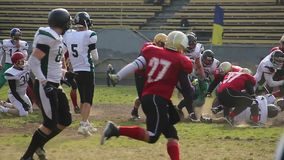 Two teams playing football on field, player tackles opponent, rough game. Stock footage stock footage