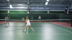 Two teams playing tennis in double game. Women and men players practicing. In game in indoor court stock video footage