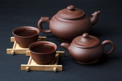 Two teapot and two cups. On a black background Royalty Free Stock Photos