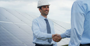 Two technical expert partners in solar photovoltaic panels, remote control performs routine operations to monitor the system using. Clean, renewable energy. The Stock Photography