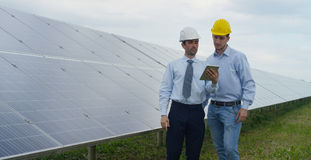 Two technical expert partners in solar photovoltaic panels, remote control performs routine operations to monitor the system using. Clean, renewable energy. The Royalty Free Stock Photos
