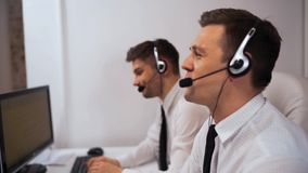 Two technical support specialist talking with customers by headsets. Two technical support specialist employee talking with customers by headsets hands-free stock video footage