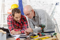 Two technician examining  mechanical part in the workshop Royalty Free Stock Photography