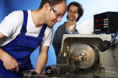 Two technicians on lathe machine in workshop Royalty Free Stock Images