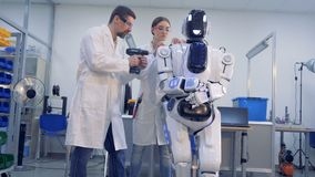 Two technicians are making adjustments to a human-like robot with a drill. 4K stock video footage