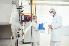 Two technologists at the food factory. Two technologists control the production process at the food factory stock photo