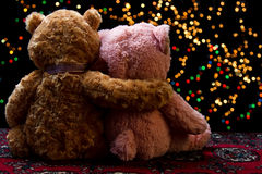 Two Teddie bear sitting holding bokeh background Stock Images