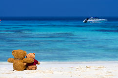 Two TEDDY BEAR brown color sitting on the beautiful beach with b Royalty Free Stock Image