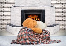 Two Teddy bear hugging and staring at the flame of the fire in the fireplace. Two Teddy bear hugging and staring at the flame stock photo