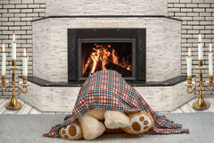 Two Teddy bear hugging under a blanket.A romantic evening by the fireplace.love under the blanket Stock Photo