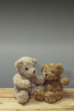 Two teddy bear sit on table wooden. Gray background for text Royalty Free Stock Photo