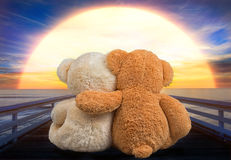 Two Teddy bear sitting on the bridge near the river and watch the sunset. Teddy bears watching the sunset stock images