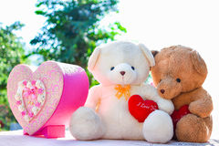 Two teddy bears hold heart shaped sitting on the table with natu Royalty Free Stock Photography