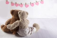 Two teddy bears hug each other with their backs to the viewer. On the wall the paper hearts hang. Valentine`s Day greeting card d. The Two teddy bears hug each Royalty Free Stock Image