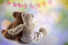 Two teddy bears hug each other with their backs to the viewer. On the wall the paper hearts hang. Valentine`s Day greeting card d. The Two teddy bears hug each Royalty Free Stock Images