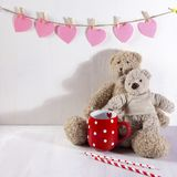 Two teddy bears hug each other with . On wall the paper hearts hang. Valentine`s Day greeting card design. The Two teddy bears hug each other with . On wall the Stock Image