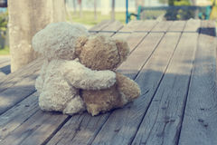 Two teddy bears hugging picnic. In the park sit on wooden. vintage style Royalty Free Stock Photo
