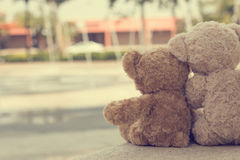Two teddy bears hugging. Two teddy bears sitting looking the fountain Royalty Free Stock Photos