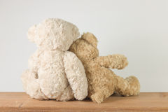 Two teddy bears love sweetness sitting on wooden table looking something. Royalty Free Stock Photography