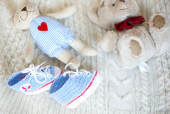 Two teddy bears and a pair of knitted handmade booties Stock Photos