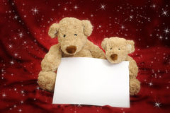 Two Teddy bears on red background with message card Stock Photos