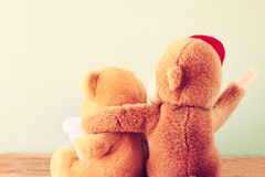 Two teddy bears on a shelf with arms around each other. Royalty Free Stock Photos