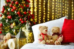 Two teddy bears siting on the bed with red candys near christmas tree. stock image