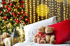 Two teddy bears siting on the bed with red candys near christmas tree. royalty free stock photo