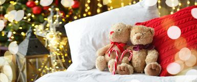 Two teddy bears siting on the bed with red candys near christmas tree. Long banner stock images