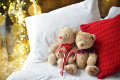 Two teddy bears siting on the bed with red candys near christmas tree. royalty free stock image