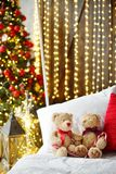Two teddy bears siting on the bed with red candys near christmas tree. royalty free stock images