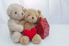 Two teddy bears sitting with red heart yarn and red house on white fabric. Two teddy bears sitting with red heart yarn and red house on white fabric copy space Royalty Free Stock Photography