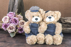 Two teddy bears in studio. Two teddy bears holding hand and take a photo in studio over flower background, love and friendship concept Royalty Free Stock Photos