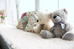 Two teddy bears and two pillows on a light windowsill Royalty Free Stock Image