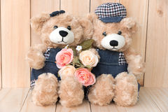 Two teddy bears on wood background Stock Photos