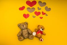 Two teddy bears on a yellow background and heart over them royalty free stock photography