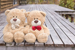 Two teddy brown bear sitting on terrace house Royalty Free Stock Photo