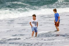 Two teen boys have fun at the beach Stock Image