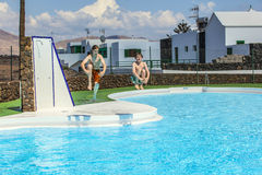 Two teen boys jump into the pool Stock Images